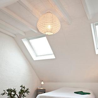 Cette image montre une grande chambre design avec un mur blanc et un sol en bois brun.