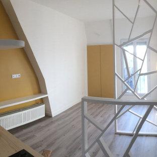 Diseño de dormitorio tipo loft, actual, pequeño, sin chimenea, con paredes amarillas, suelo de linóleo y suelo gris