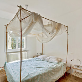 Aménagement d'une chambre d'amis méditerranéenne avec un mur blanc, un sol en bois brun et un sol marron.