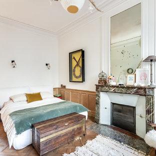 Aménagement d'une grande chambre parentale éclectique avec un mur blanc, un sol en bois brun, une cheminée standard et un manteau de cheminée en pierre.