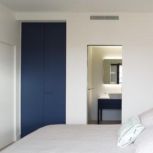 Exemple d'une chambre tendance avec un mur blanc et un sol beige.