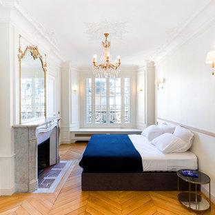 Cette image montre une chambre traditionnelle avec un mur blanc, un sol en bois clair, une cheminée standard et un sol beige.