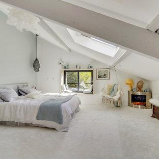 Réalisation d'une grand chambre design avec un mur blanc, un manteau de cheminée en métal, un sol blanc et une cheminée d'angle.