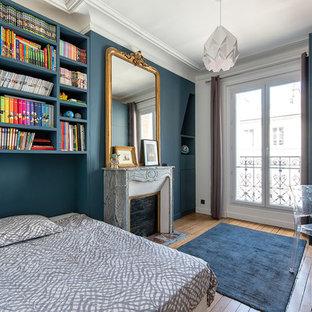 Exemple d'une chambre chic avec un mur bleu, un sol en bois brun, une cheminée standard, un manteau de cheminée en pierre et un sol marron.