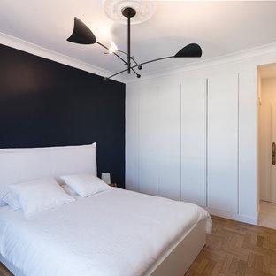 Imagen de dormitorio principal, actual, grande, sin chimenea, con paredes negras, suelo marrón y suelo de madera en tonos medios