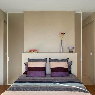Inspiration pour une petit chambre design avec un mur beige, un sol en bois brun et aucune cheminée.