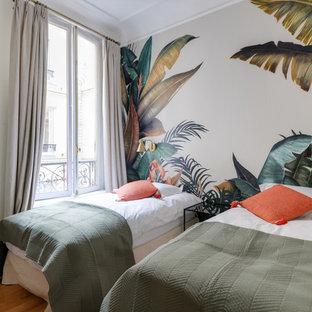 Aménagement d'une chambre d'amis contemporaine avec un mur blanc, un sol en bois brun et un sol marron.