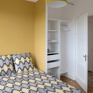 Mid-sized scandinavian master bedroom in Other with yellow walls, medium hardwood floors and no fireplace.