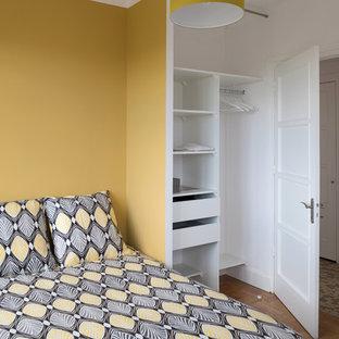 Modelo de dormitorio principal, nórdico, de tamaño medio, sin chimenea, con paredes amarillas y suelo de madera en tonos medios