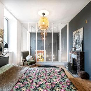 Idee per una grande camera matrimoniale minimal con pareti grigie, pavimento in legno massello medio, camino classico e cornice del camino in pietra