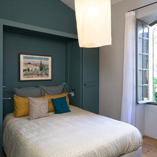 Idée de décoration pour une chambre parentale méditerranéenne de taille moyenne avec un mur bleu, un sol en bois clair et aucune cheminée.