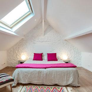 Cette image montre une chambre parentale design de taille moyenne avec un mur blanc, un sol marron et un sol en bois clair.