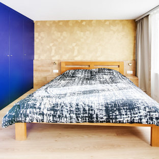 Imagen de dormitorio principal, minimalista, de tamaño medio, sin chimenea, con paredes azules, suelo laminado y suelo violeta