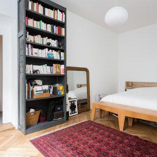 Inspiration pour une chambre parentale design de taille moyenne avec un mur blanc, un sol en bois brun, aucune cheminée et un sol beige.