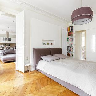 Aménagement d'une grande chambre parentale contemporaine avec un mur blanc et un sol en bois brun.