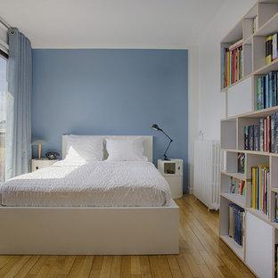 Exemple d'une chambre tendance avec un mur bleu, un sol en bois brun et un sol marron.