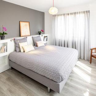 Exemple d'une chambre parentale tendance de taille moyenne avec un mur blanc, un sol en bois clair et un sol beige.