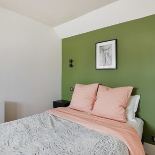 Design ideas for a mid-sized scandinavian master bedroom in Paris with green walls, light hardwood floors, no fireplace and brown floor.