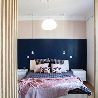 This is an example of a contemporary bedroom in Paris with pink walls, medium hardwood floors and brown floor.