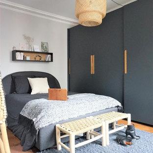 Cette image montre une chambre design avec un mur blanc, un sol en bois brun et un sol marron.
