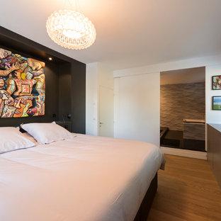 Exemple d'une chambre tendance avec un mur blanc, un sol en bois clair et un sol beige.