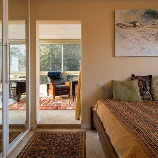 На фото: большая гостевая спальня в стиле кантри с бежевыми стенами, полом из известняка, печью-буржуйкой и фасадом камина из металла с