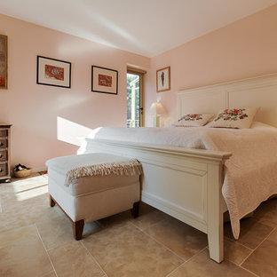 Diseño de dormitorio principal, romántico, grande, con paredes beige, suelo de piedra caliza, estufa de leña y marco de chimenea de metal