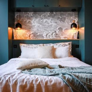 Ejemplo de dormitorio principal, contemporáneo, grande, con paredes grises, suelo de madera clara, chimenea de esquina, marco de chimenea de piedra y suelo marrón