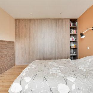 Lantlig inredning av ett mellanstort huvudsovrum, med orange väggar och ljust trägolv