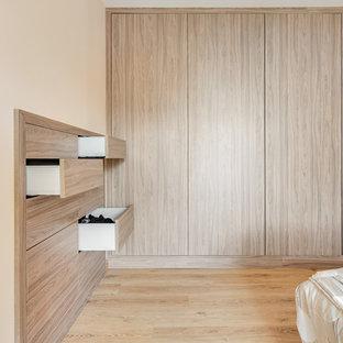 Ejemplo de dormitorio principal, de estilo de casa de campo, de tamaño medio, sin chimenea, con parades naranjas y suelo de madera clara