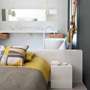 Cette image montre une grand chambre parentale design avec un mur vert et béton au sol.
