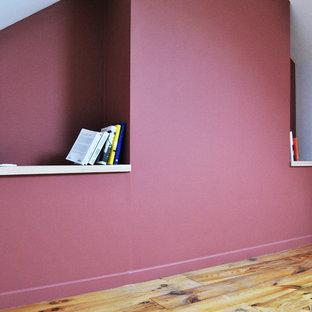 Cette image montre une chambre parentale design de taille moyenne avec un mur rouge, un sol en bois brun et aucune cheminée.