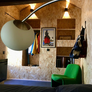 Design ideas for a mid-sized beach style guest bedroom in Lyon with concrete floors, black floor, wood and wood walls.