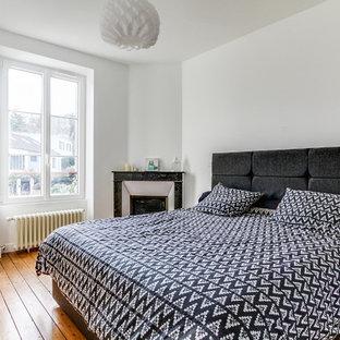 Idee per una camera matrimoniale nordica con pareti bianche, pavimento in legno massello medio, camino ad angolo, cornice del camino in pietra e pavimento beige
