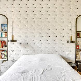 Exemple d'une chambre d'amis tendance avec un mur beige, un sol en bois brun et un sol beige.