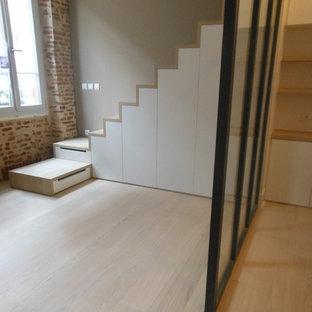 Imagen de dormitorio principal, minimalista, grande, con paredes multicolor, suelo de madera clara, chimenea tradicional, marco de chimenea de yeso y suelo beige