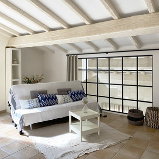 Photo of a large beach style guest bedroom in Nice with blue walls, terra-cotta floors, no fireplace and beige floor.