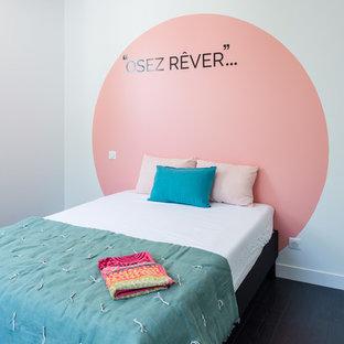 Imagen de dormitorio principal, actual, de tamaño medio, sin chimenea, con paredes rosas, suelo de madera oscura y suelo negro