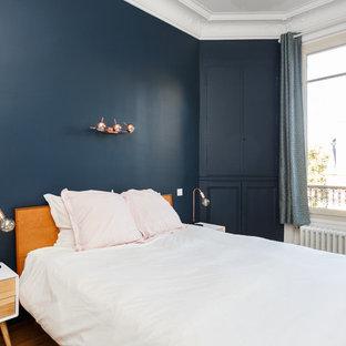 Foto di una camera matrimoniale scandinava di medie dimensioni con pareti blu, pavimento in legno massello medio, camino classico, cornice del camino in pietra e pavimento marrone