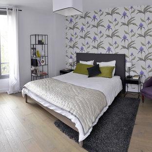 Aménagement d'une chambre parentale contemporaine de taille moyenne avec un mur multicolore et un sol en bois clair.