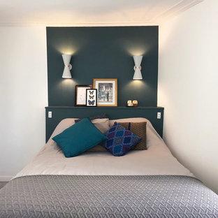 Diseño de dormitorio principal, moderno, de tamaño medio, con paredes verdes, suelo de linóleo, chimenea de esquina, marco de chimenea de piedra y suelo gris