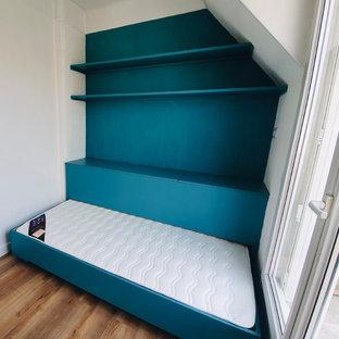 Diseño de dormitorio tipo loft, contemporáneo, pequeño, con paredes azules y suelo laminado