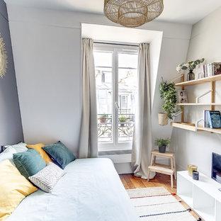 Cette photo montre une chambre d'amis tendance de taille moyenne avec un mur blanc, un sol en bois brun, un sol marron et aucune cheminée.