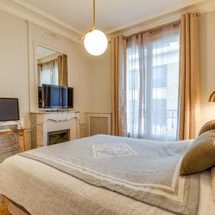 Exemple d'une chambre parentale tendance de taille moyenne avec un mur blanc, un sol en bois clair, une cheminée standard, un manteau de cheminée en pierre et un sol marron.