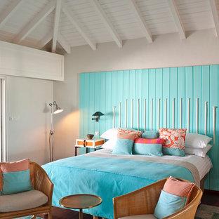 Cette photo montre une chambre parentale bord de mer de taille moyenne avec un mur gris, un sol en bois brun et aucune cheminée.