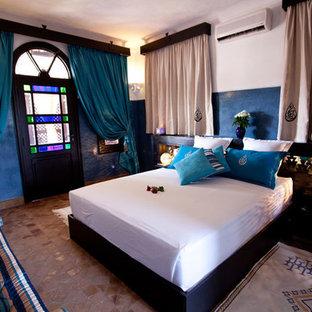 Immagine di una grande camera matrimoniale mediterranea con pareti blu, pavimento in terracotta e nessun camino