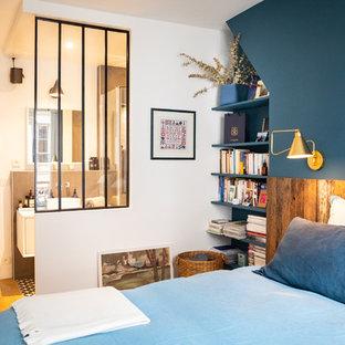 Cette image montre une chambre design avec un mur bleu, un sol en bois brun et un sol marron.