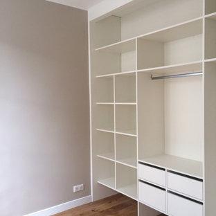 Idées déco pour une petite chambre parentale moderne avec un mur beige, un sol en bois clair et un sol beige.