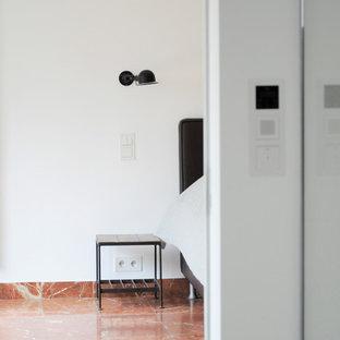 Modelo de dormitorio principal, actual, extra grande, con paredes blancas, suelo de mármol y suelo rojo