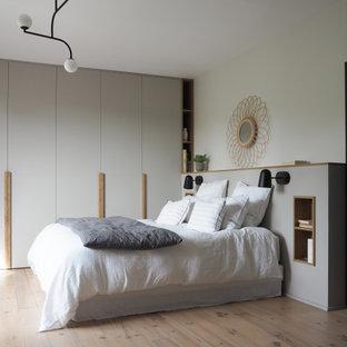 Cette photo montre une chambre parentale tendance de taille moyenne avec un mur blanc, un sol en bois brun et un sol beige.